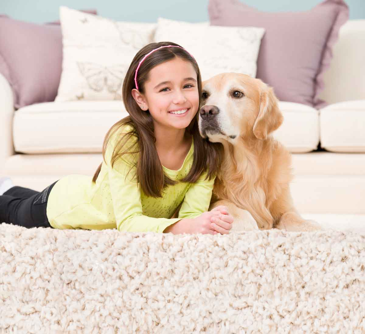 girl and dog lying on carpet in Raleigh, NC