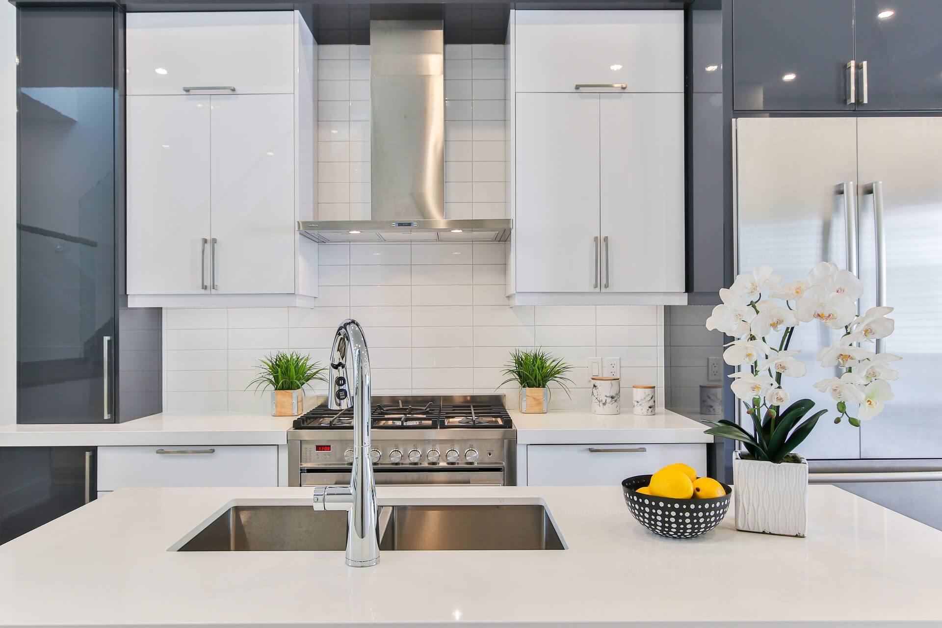 kitchen with sink and white cabinets with fridge